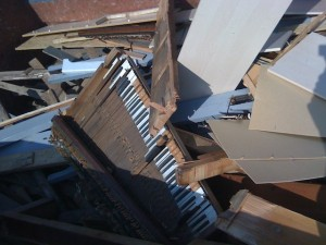 Antique piano in a dumpster